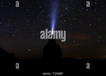 Silhouette of man with headlamp at night - Stock Image