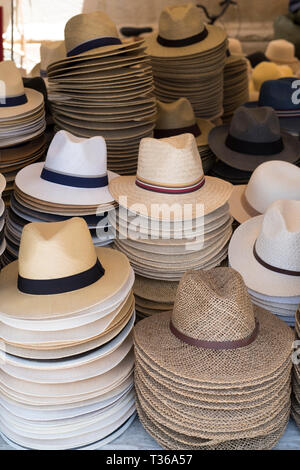 Panama and straw sun hats on display for sale on market stall at the old street market - Mercado -  in Ortigia, Syracuse, Sicily - Stock Image