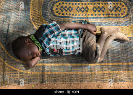 Samba village, Yako Province, Burkina Faso: a boy sleeping during a hot afternoon. - Stock Image