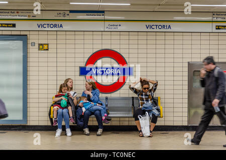 People sit on a bench on the platform at Victoria London Underground tube station. - Stock Image