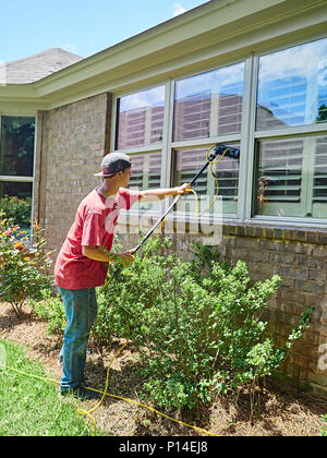 White male adult window washer employee or worker washing windows on a residential house or home in suburban America. - Stock Image