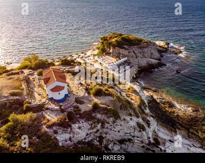 Thasos Island beach bar and church in sunset light, Greece - Stock Image