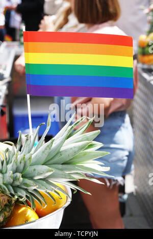 rainbow flag as bar decoration at gay pride event or csd christopher street day celebration - defocused unrecognizable people in the background - Stock Image