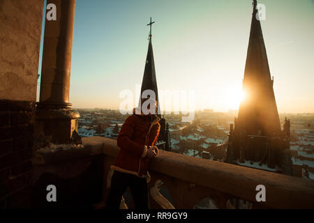 A young man stands on the balcony and looks at the cityscape against the background of church towers at sunset. - Stock Image
