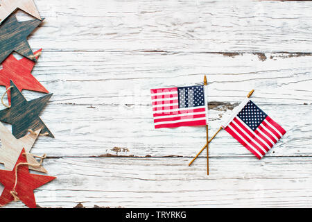 Fourth of July Background. Two American flags and a border of a wooden star banner over a rustic white wood table / background to mark America's Indep - Stock Image