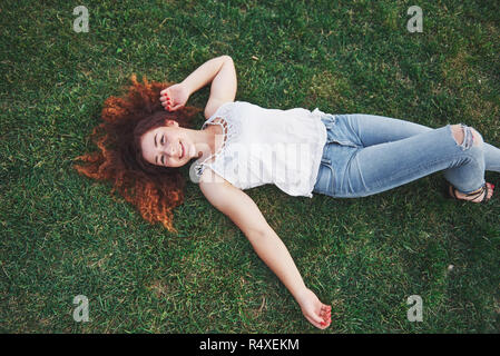 Relaxing girl with red, lying on the grass. Woman relaxes outdoors. - Stock Image