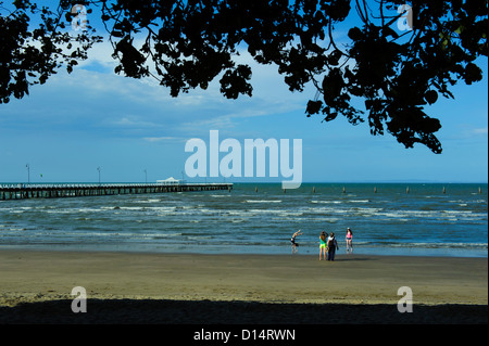 Three children and an adult on the beach of Moreton Bay, with historic Shorncliffe Pier in background. Brisbane, - Stock Image