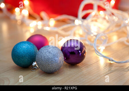 Four colorful christmas lights with tangled white lights on the floor - Stock Image