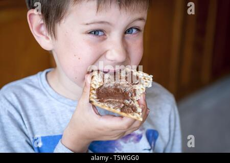 A closeup portrait of a cute blue-eyed child eating a matzoh cracker with chocolate spread. - Stock Image