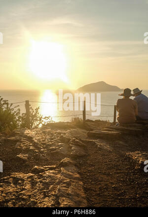 Hatted Couple enjoying the ocean views from Cape Sounion (Temple of Poseidon ) as the Sun begins to set. East Attica, Greece. - Stock Image