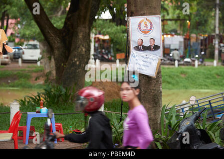 Siem Reap, Cambodia. Saturday, 28th July 2018: A motion blurred young woman stares at the camera with Cambodian general election campaign poster featuring Peoples Party candidates in the background. The polls open on Sunday 29th July. Credit: Nando Machado/Alamy Live News - Stock Image