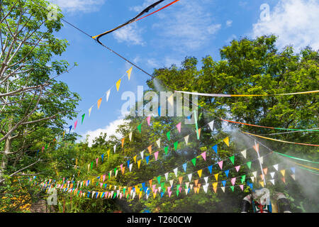 Colorful small flags in the festival, on blue sky background. - Stock Image