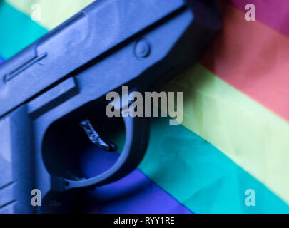 Automatic pistol handgun with gay lesbian LGBT homosexual pride rights flag colors. - Stock Image