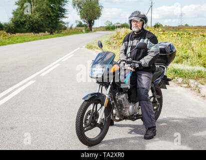 elderly motorcyclist wearing a jacket and glasses with a helmet sitting on his motorcycle on the open road on sunny summer day - Stock Image