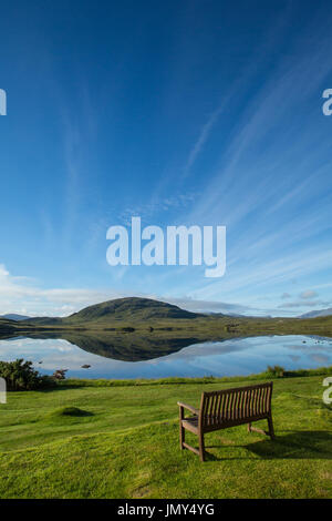 Looking over Loch Morsgail on a blue summer day with the hill called Scalabhal behind and reflected in the water. Thin white clouds streak the sky - Stock Image