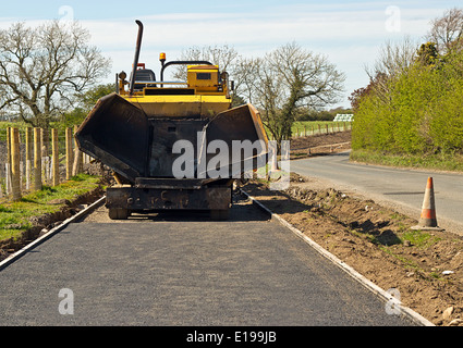 Small scale construction machinery laying a roadside footpath for greater pedestrian safety - Stock Image