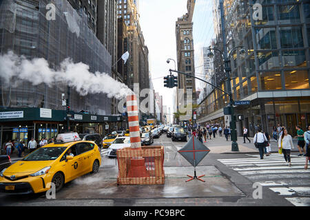 steam leak coming out a temporary chimney at a busy midtown 42nd street in Manhattan - Stock Image