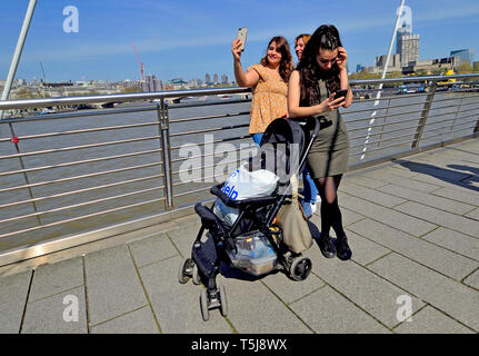 London, England, UK. Young women on the Millennium Bridge with their mobile phones, taking a selfie - Stock Image