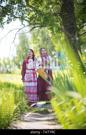 Two young women in traditional russian clothes walking along the path and talk. One of them holding balalaika - vertical shot - Stock Image