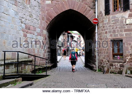 Pilgrim leaving early morning through Notre Dame door on their way to Santiago on the wayof St-James, St-jean-pied-de-port, France, June 2019 - Stock Image