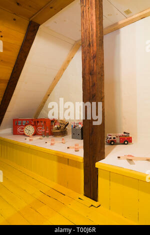 Vintage toys and empty Coca-Cola bottles on raised platform in attic room with yellow painted pinewood floorboards inside old circa 1760 home interior - Stock Image