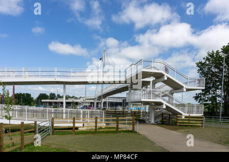 Modern pedestrian footbridge crossing the main A45 and leading to Rushden Lakes Shopping Centre, Northamptonshire, UK - Stock Image