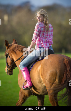 Teenage girl riding horse in field - Stock Image