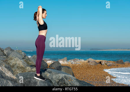 woman doing a arm stretch warm up exercise outside on rocks with blue sky - Stock Image