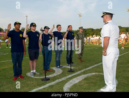 MUNFORD, Tenn. (Aug. 24, 2018) Lt. j.g. Wilfred Noel gives the oath of enlistment to Future Sailors during an Armed Forces football game held at Munford High School. The oath of enlistment is a military oath made by members of the U.S. Armed Forces when they initially join the U.S. military or reenlist. The Future Sailors are (from left to right) Patrick Smith from Covington, Tenn., Aiden Baird from Munford, Tenn., Quentin Morris from Covington, Tenn., Anthony Hilbert from Covington, Tenn., and Justin Ansley from Millington Tenn. (U.S. Navy photo by Mass Communication Specialist 2nd Class Kyle - Stock Image