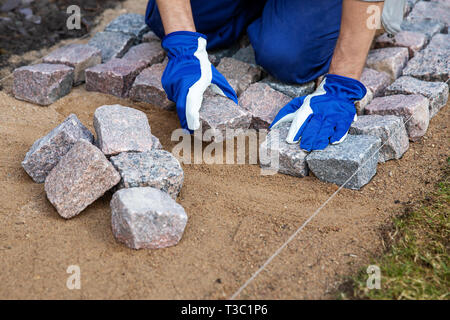 garden path construction - worker laying granite stone pavers - Stock Image