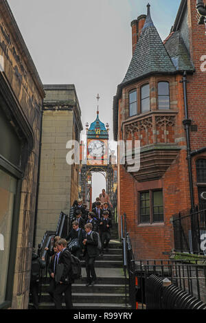 A party of visiting school children walking under the Victorian clock on Newgate, Chester, the County town of Cheshire, England, UK - Stock Image