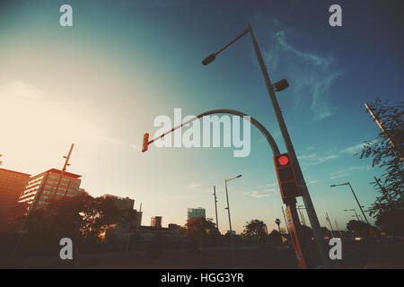 Wide angle shot of red traffic light on street lantern near highway, sunset and evening in residential Forum district - Stock Image