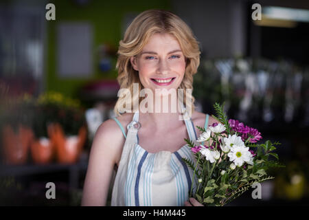 Happy female florist holding bunch of flowers in flower shop - Stock Image