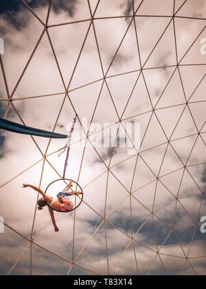 Beautiful young blonde people girl in aerial fitness exercises training for exibition show and steel building and clouds in background - warm colours  - Stock Image