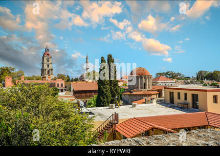 Skyline of the ancient city of Rhodes Greece, on the island of Rhodes showing a minaret, church and rooftops - Stock Image