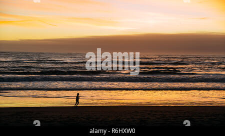 Silhouette of person running on beach at Caparica, near Lisbon, Portugal at sunset. - Stock Image