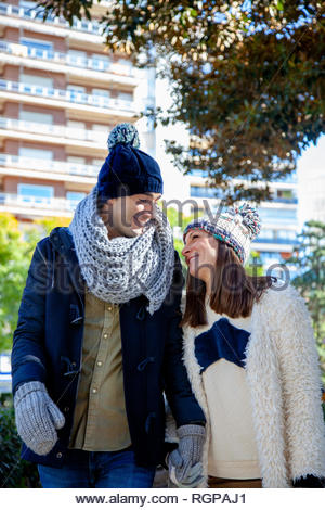 Young bride and groom walk hand in hand through a public park dressed in winter wool hats. - Stock Image
