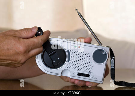 person winding up portable radio - Stock Image