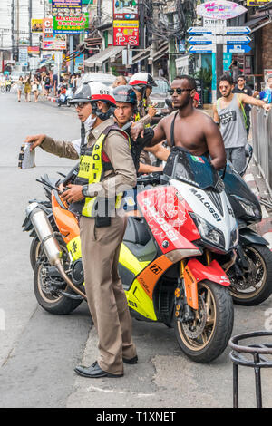 Phuket, Thailand 17th January 2019: Police checking tourists driving licenses in Patong Beach. Police often fine tourists for traffic offences. - Stock Image