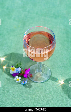 Glass with cold rose wine and wild flowers in summer sunny day close up - Stock Image