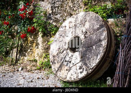 Old wheel with wood sticks nearby - Stock Image