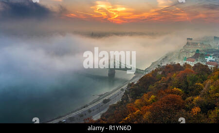 Budapest, Hungary - Panoramic view of mysterious foggy sunrise with Liberty Bridge (Szabadsag hid) and hazy skyline of Budapest at autumn morning - Stock Image