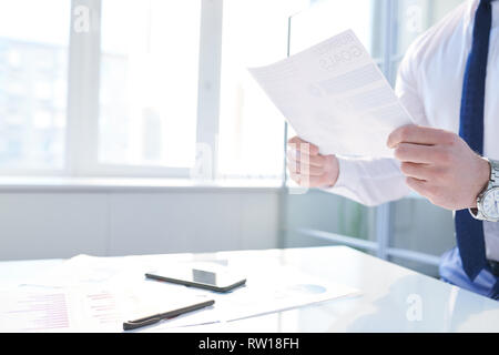 Reading paper in office - Stock Image