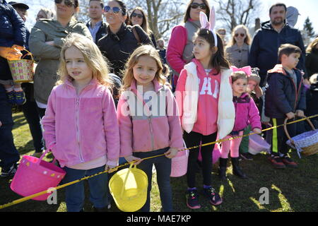 North Merrick, New York, USA. March 31, 2018. Young girls, many wearing pink, and boys wait behind yellow tape for start of traditional Easter Egg Hunt at the Annual Eggstravaganza, held at Fraser Park and hosted by North and Central Merrick Civic Association (NCMCA). Credit: Ann E Parry/Alamy Live News - Stock Image