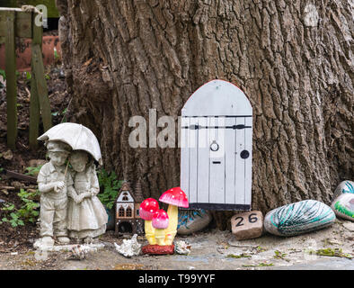 Garden ornaments around the base of large tree UK - Stock Image