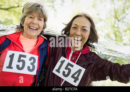 Portrait smiling, confident active senior women finishing sports race, wrapped in thermal blanket - Stock Image