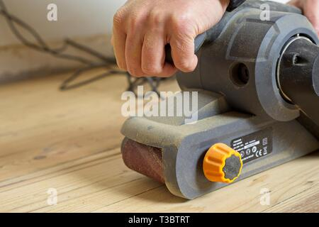 Female using a belt sander on a pine wooden floor during DIY and home renovations - Stock Image