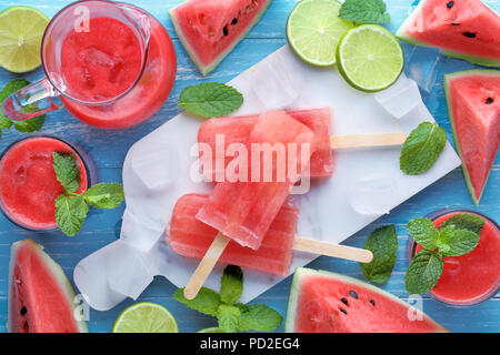 Watermelon,slices of lemon and watermelon juice on table - Stock Image