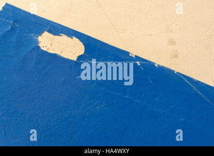 Blue painted wall with flaking paint. Diagonal blue and white decoration design background for home improvement - Stock Image