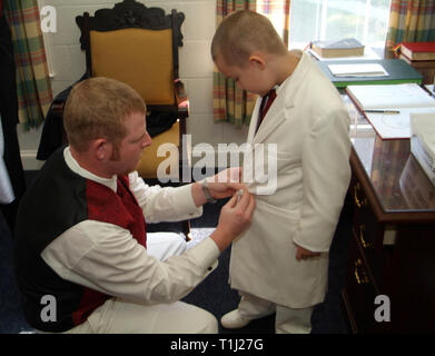man helping child to get dressed in his Sunday best - Stock Image